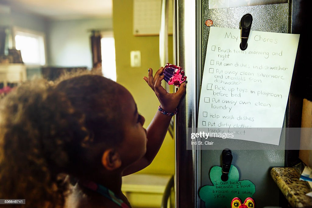 Girl looking at list of chores on fridge : Stock Photo