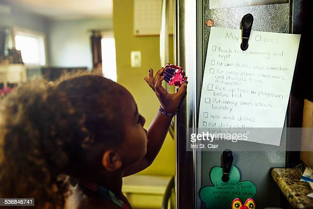 Girl looking at list of chores on fridge