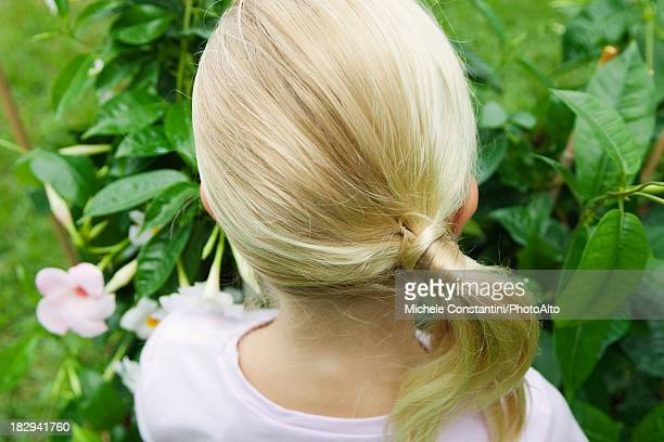 Girl looking at mandevilla, rear view