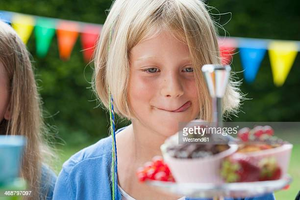 Girl looking at muffins on a birthday party