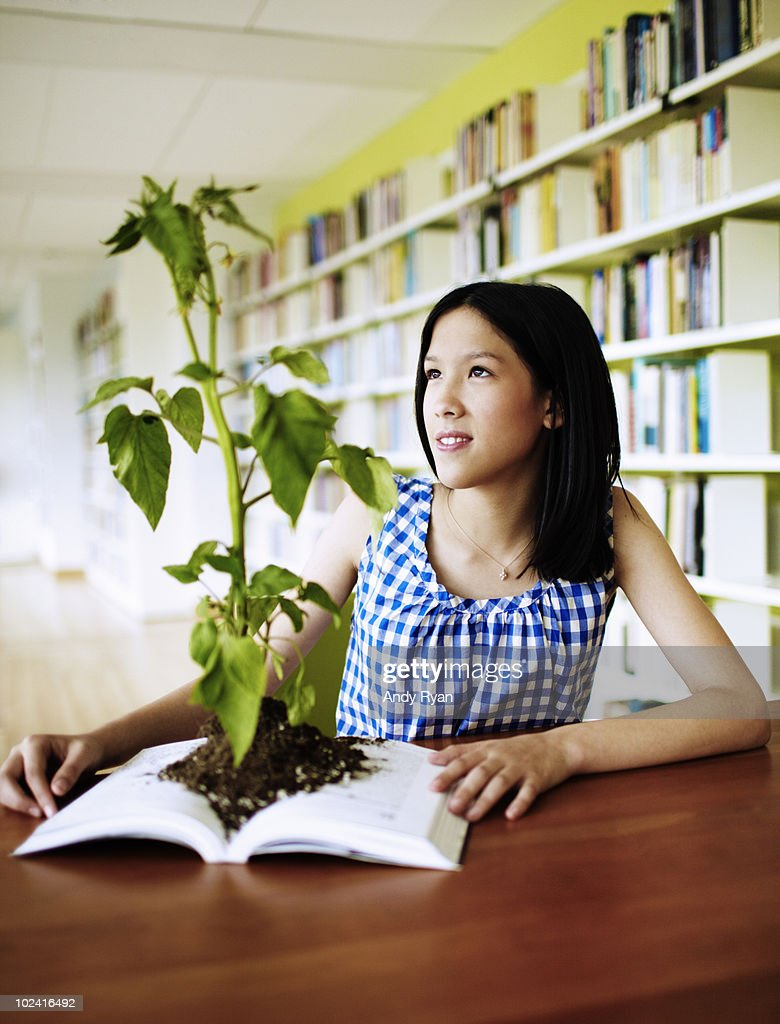 girl looking at plant growing from book : Stock Photo