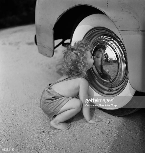 Girl looking at reflection in hubcap