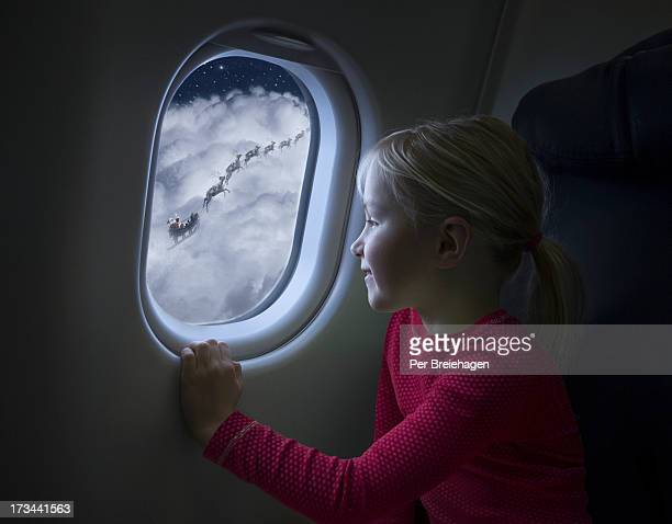 A girl looking at Santa flying by airplane window