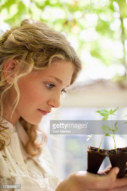Fille regardant de graines plateau en plastique la croissance