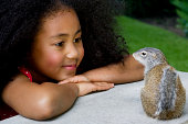 Girl (5-7) looking at squirrel outdoors, close-up