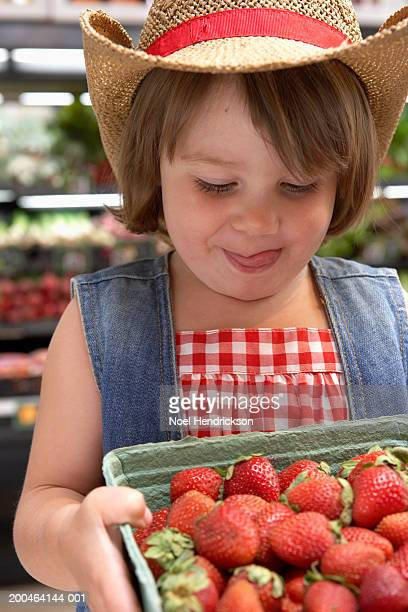 Girl (3-5) looking at strawberries in supermarket, close-up