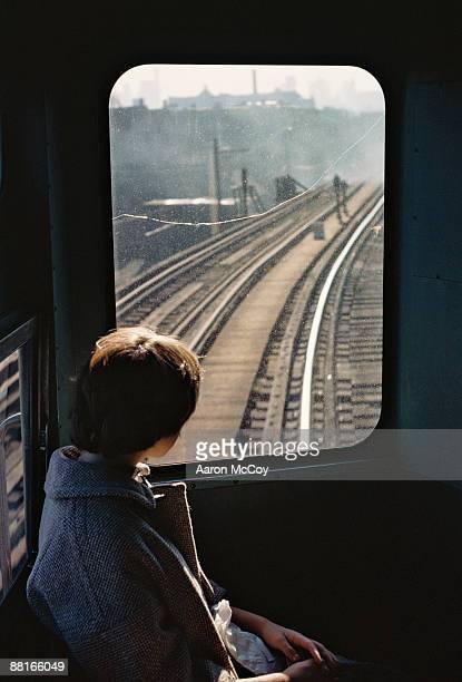 Girl looking at train tracks through window