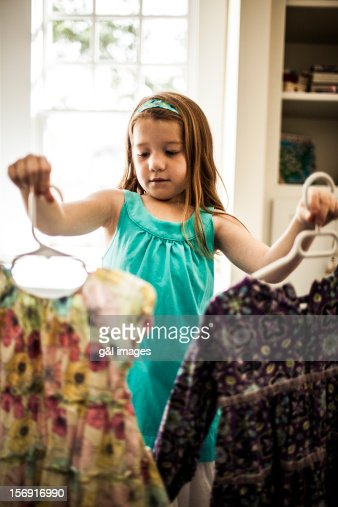girl (6yrs) looking at which dress to wear : Bildbanksbilder