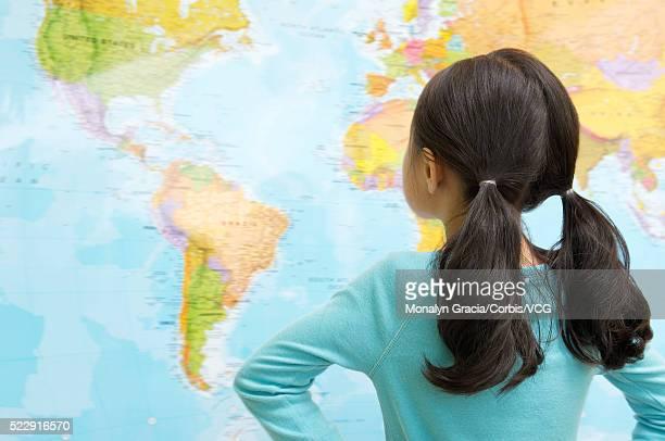 Girl looking at world map
