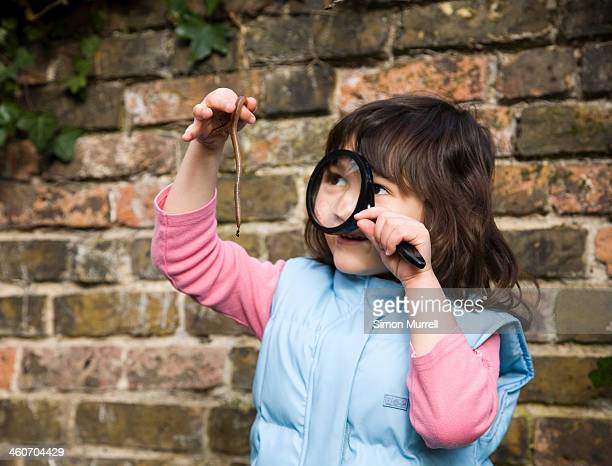 Girl looking at worm with magnifying glass