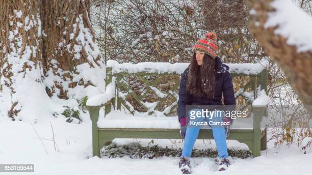 Girl looking away on bench at snowy park