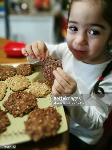 Girl Looking Away While Eating Cookies At Home