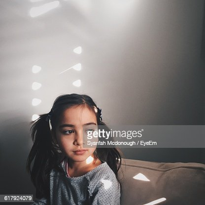 Girl Looking Away While Sitting On Couch