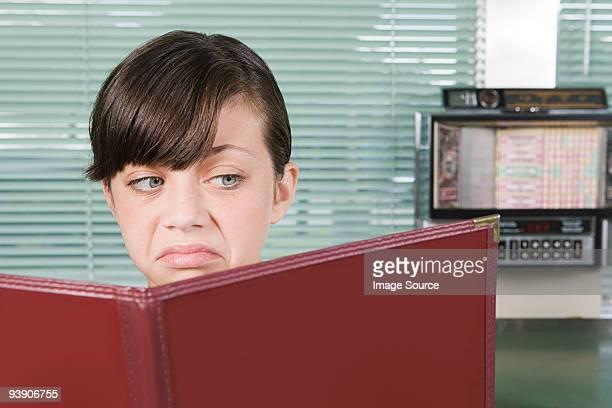 Girl looking disgusted with menu