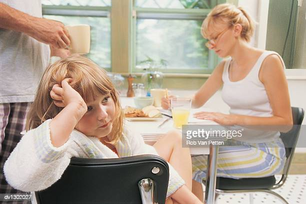 Girl Looking Fed Up and Woman Studying at Kitchen Table