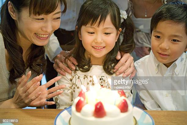 Girl looking her birthday cake with her family