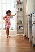 Girl (4-6) looking in kitchen fridge
