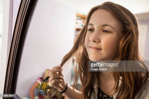 Girl looking in mirror, touching hair
