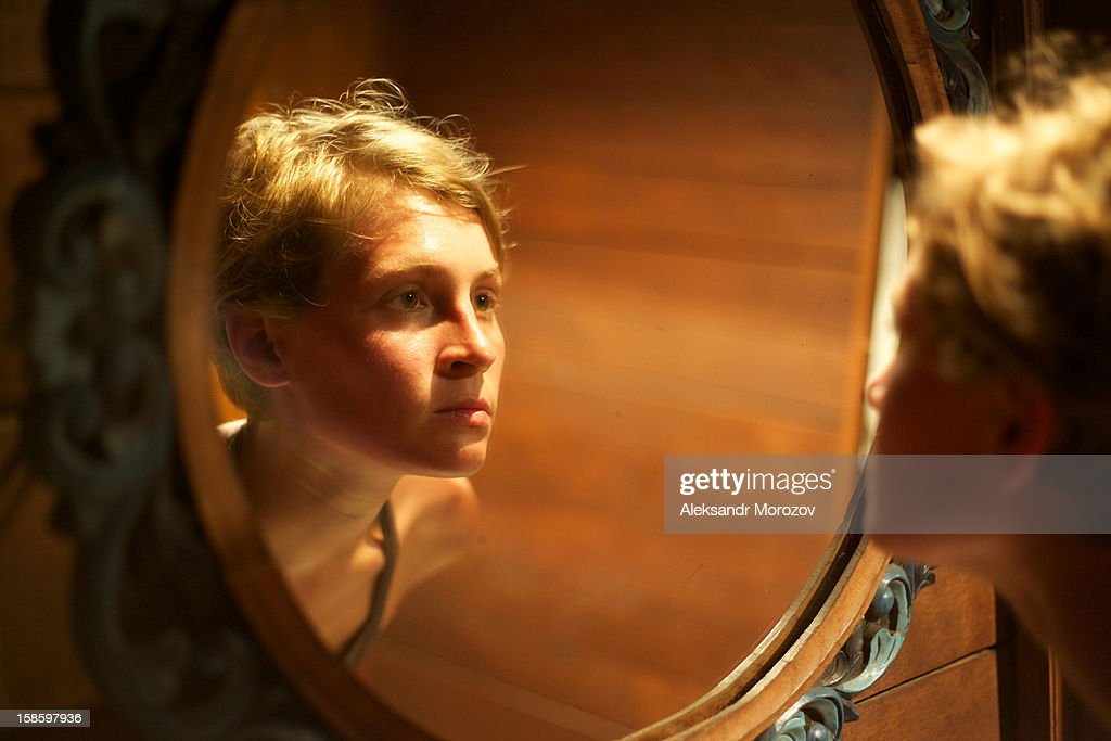 Girl looking in the mirror : Stock Photo