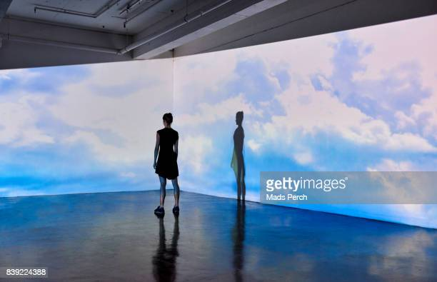 Girl looking into a large scale projected image of Skies