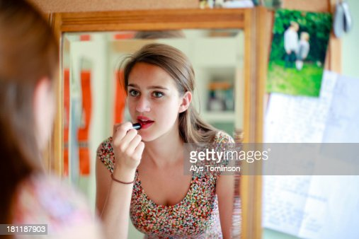 Girl looking into a mirror applying lipstick