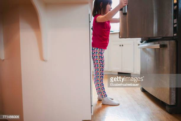 Girl looking into a refrigerator