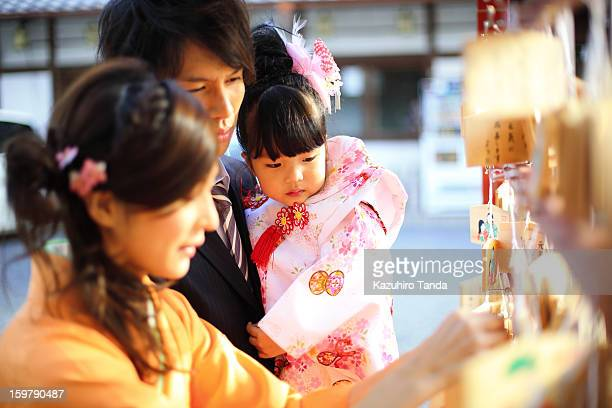 Girl looking mother put a wooden plaque