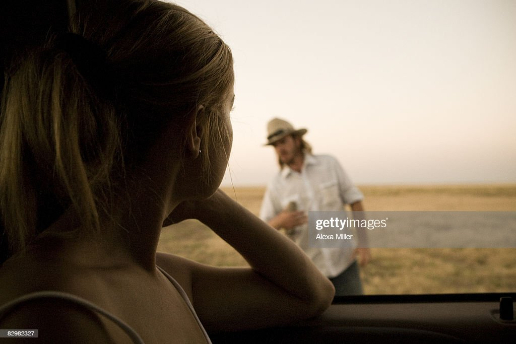 girl looking out car window at guy stock photo getty images