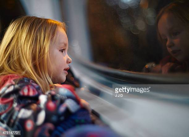Girl looking out of a bus window during a journey at night