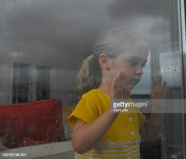 Girl (2-4) looking out of rain covered window, view through glass