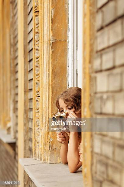 girl looking out of the window with opera glasses