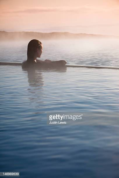 Girl looking out over misty water in hot spring