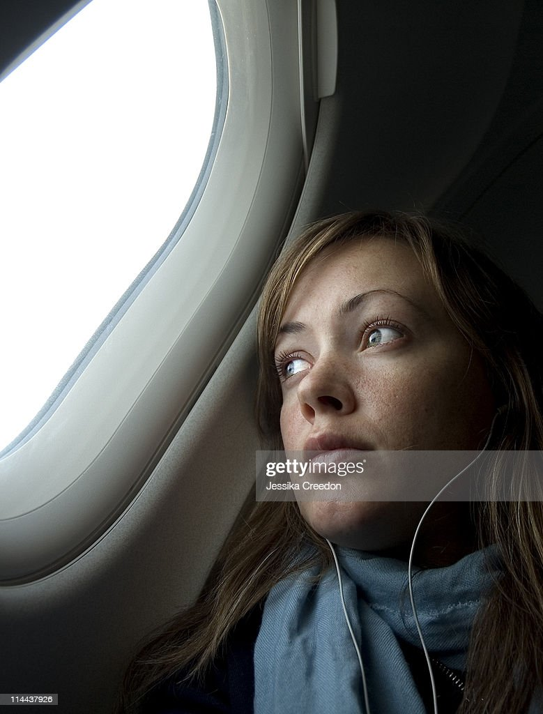 Girl looking out through plane window.