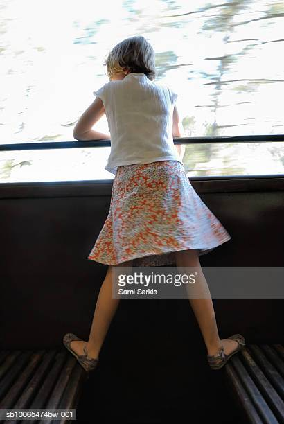 Girl (6-7) looking out window of speeding train, rear view