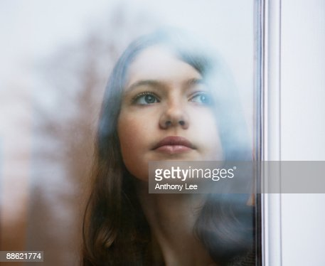 Girl looking out window : Stock Photo