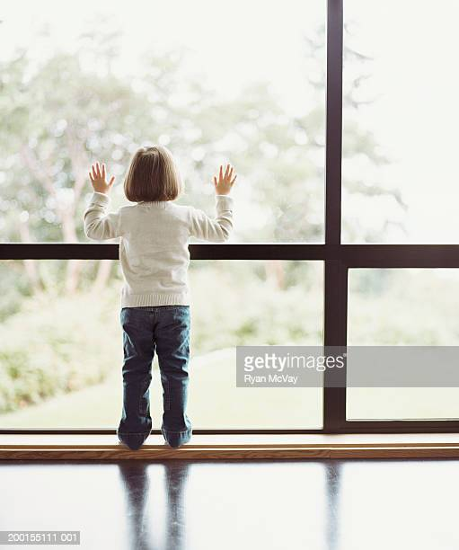 Girl (2-4) looking out window, rear view