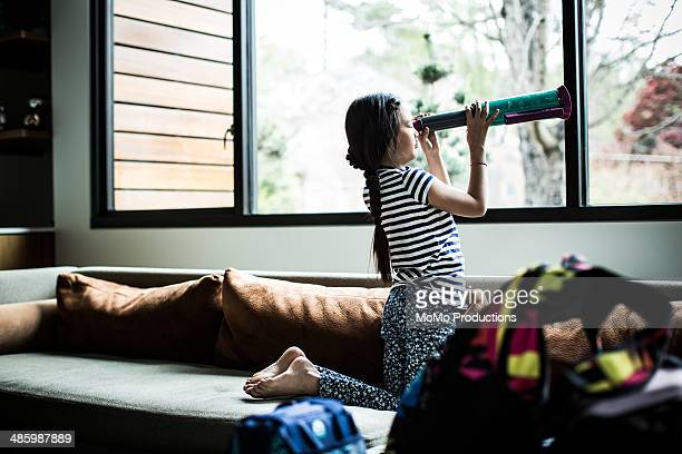girl looking out window with telescope
