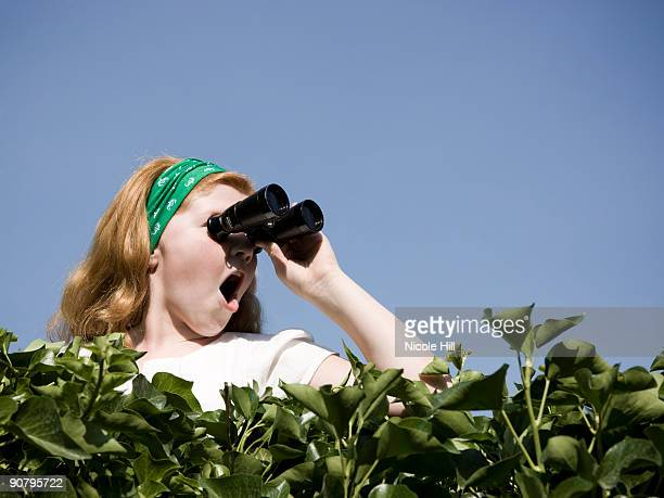 girl looking over a hedge with binoculars