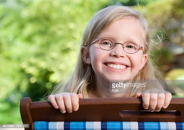 Girl (8-9) looking over deckchair, smiling, portrait