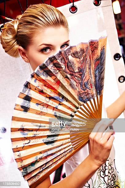 Girl looking over foldable fan