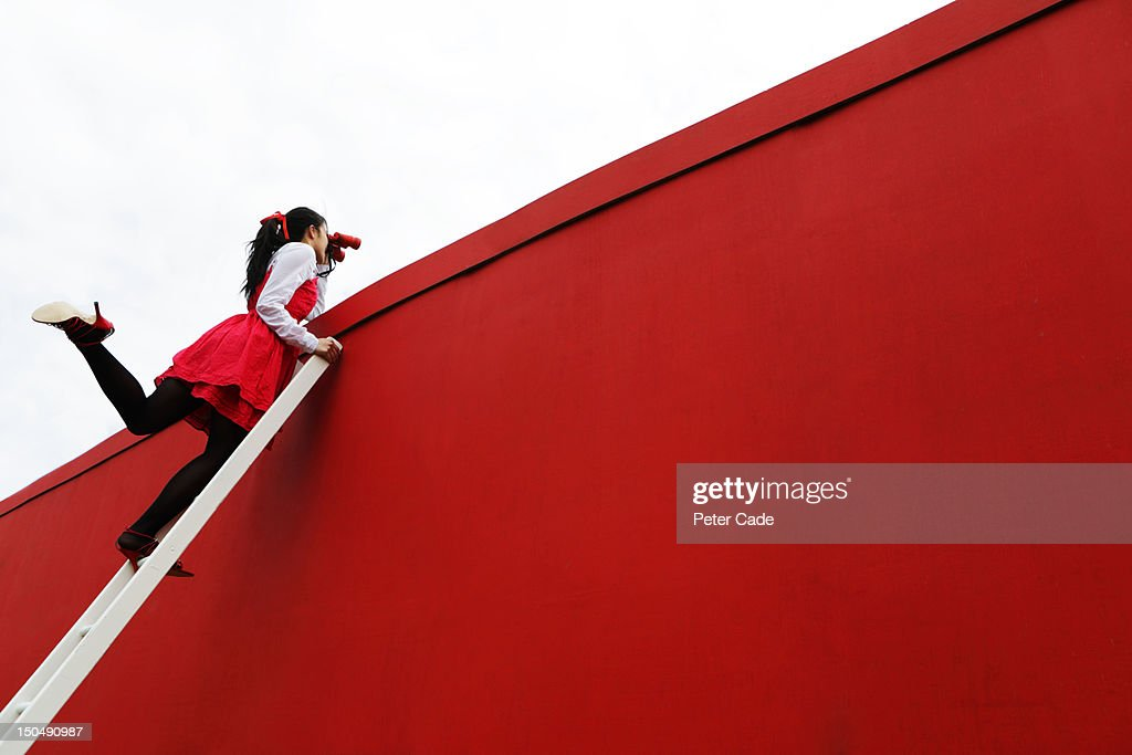 Girl looking over red wall with binoculars : Stock Photo