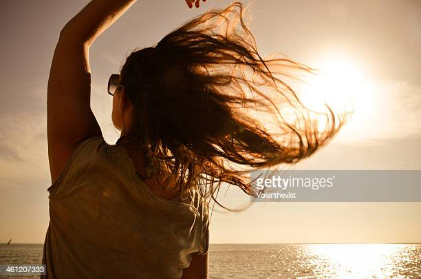 Girl looking the sea w/ hair in the wind at sunset