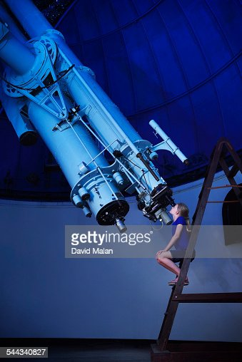 Girl looking through a large telescope