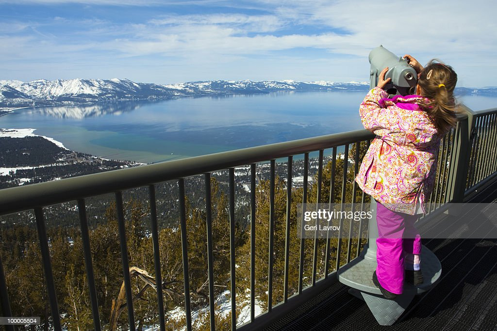 Girl looking through a telescope at Lake Tahoe : Stock Photo