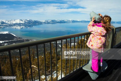 Girl looking through a telescope at Lake Tahoe : Stockfoto