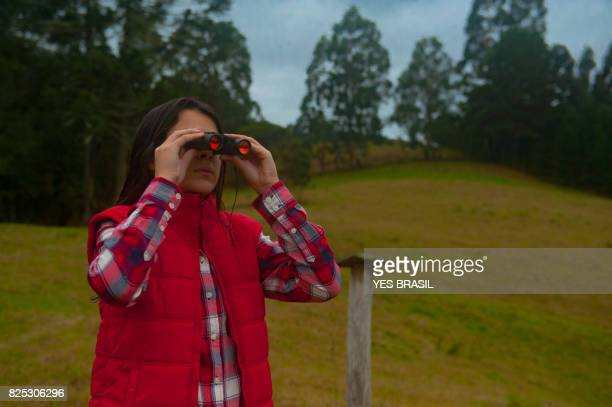 Girl looking through binoculars to observe the birds of nature