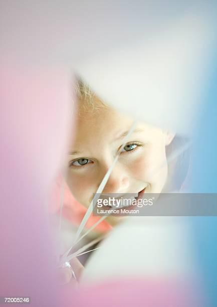 Girl looking through bunch of balloons