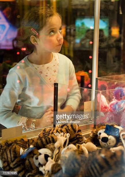 Girl looking through glass of toy grabbing game