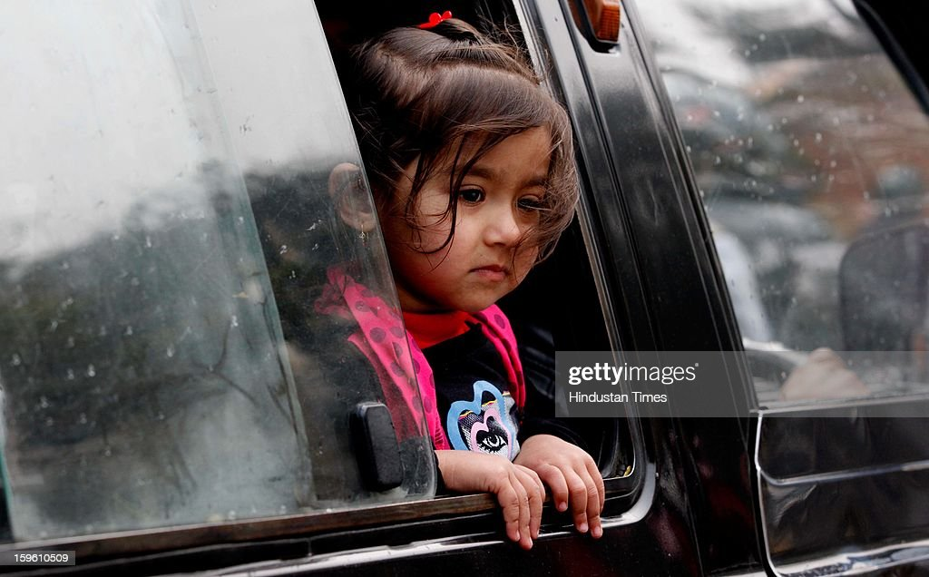 A girl looking through glass window during rainfall on January 17, 2013 in New Delhi, India. Capital witnessed light rain and chilly winds even though temperatures were above average.