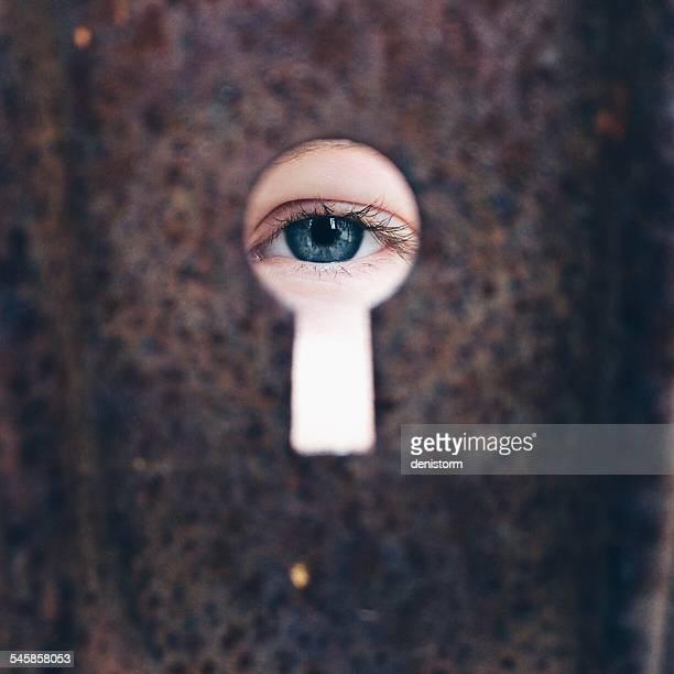Girl (8-9)  looking through keyhole